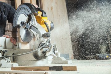 A close-up like a working circular saw cuts a board, sawdust flies to the sides