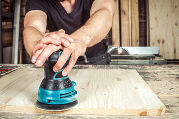Man builder processes the board with a random orbit sander in the workshop