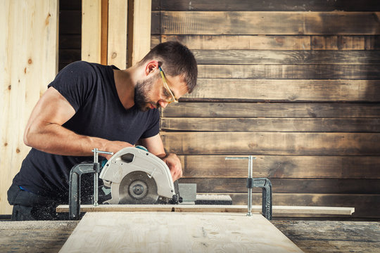 The man builder uses a modern circular   saw in order to saw the board in the workshop
