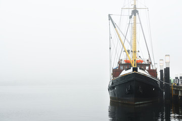 Fishing boat moored to a pier under heavy fog
