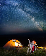 Happy male hiker showing red-haired lady at the stars and Milky way in the sky. Couple sitting near the lighting tent at night. Long exposure
