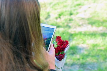 Woman taking picture of a red roses with smartphone.