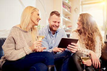 Friends sitting on sofa and using tablet in living room