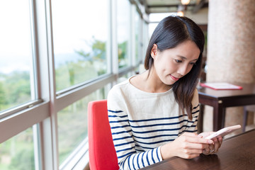 Woman use of mobile phone in japanese cafe