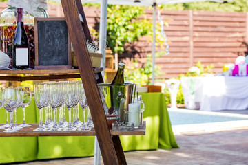 Composition of catering stand with glasses, bottlesand other prepared for outdoor party.