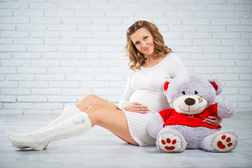 Pregnant woman sitting on the floor with a teddy bear