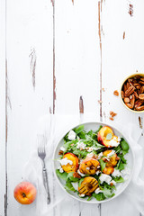 Fresh salad with grilled peach halves, arugula and burrata on a plate on white distressed wooden background. Top view. Vertical composition with copy space. Summer food concept