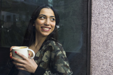 View through window of smiling woman looking away holding coffee cup in cafe.