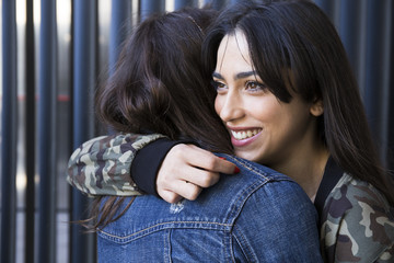 Cheerful young woman looking away and hugging with her friends at the wall.