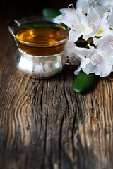 tea and White rhododendron on wood - wooden table
