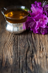 tea and purple rhododendron on wood - wooden table