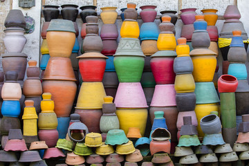 Colorful clay pots on the ground. Tourist art and craft market. Ubud in Bali Island, Indonesia