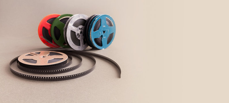 Vintage collection 8 mm cinema film reel. Retro design colorful celluloid accessories for home video projector. Gray background, selective focus