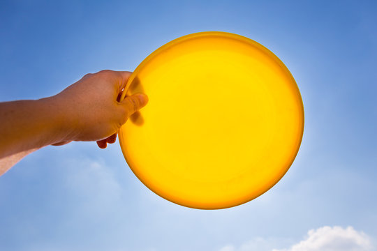 male hand catching holding yellow frisbee disc against blue sky background