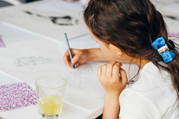 Unrecognizable little girl drawing a picture on paper. Close-up shot.