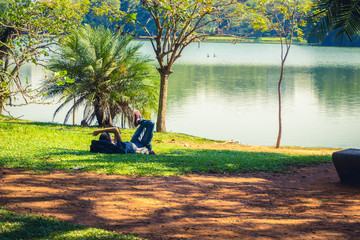 Man lying and relaxing in Ibirapuera Park - Sao Paulo, Brazil.