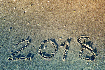 Happy new year 2018, lettering on sand on the beach, toned