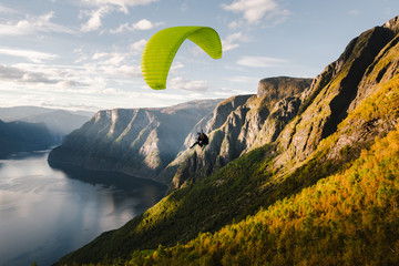 Paraglider silhouette flying over Aurlandfjord, Norway