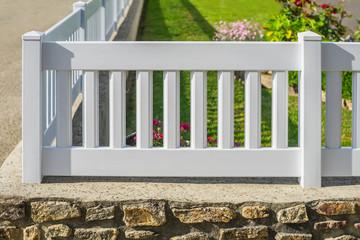 Gartenzaun aus Kunststoff in Weiß aus PVC auf einer Natursteinmauer - Plastic garden fence in white PVC on a natural stone wall