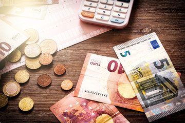 Euro banknotes and coins with bills to pay