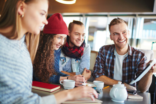 Group of joyful students gathered together in small coffeehouse and doing homework