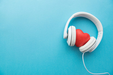 White headphones with red heart sign in the middle on blue surface