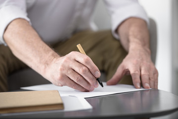 senior businessman making notes, cropped image