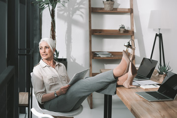 Senior business woman on worklace reading with her legs on table