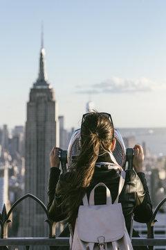 Tourist woman using binoculars in rooftop.