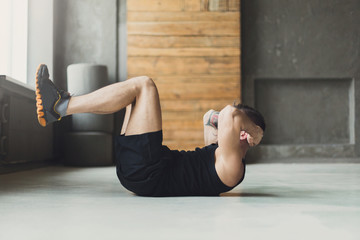 Young man fitness workout, sit-up crunches for abs