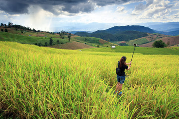 lady taking photo in rice field and mountain during storm coming