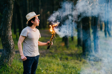 Native american redskin indian peruvian indigenous man in straw hat invoking spirits in forest outdoor in summer with burning and smoking wooden torch at hand. Shaman rite. Spiritual ceremony. Witcher