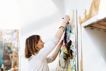 Woman hanging up painted fabric, in creative studio