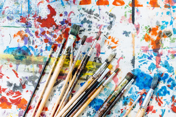 Still life of paintbrushes on colourful painted surface, overhead view