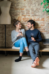 Young couple sitting on bench with red wine