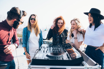 Young man using mixing desk at roof party, group of young women standing around him