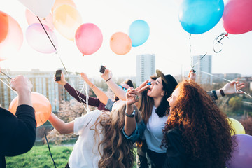 Group of friends taking selfie while holding helium balloons