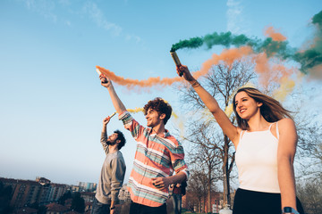 Group of friends on roof, holding colourful smoke flares