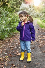 Portrait of young girl on rural pathway, looking through magnifying glass