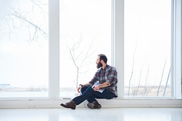 Young male designer looking through window from design studio window seat