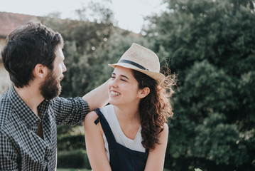 Man trying trilby hat on girlfriend, Arezzo, Tuscany, Italy