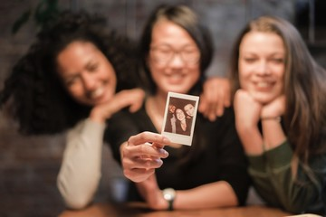 Friends holding instant film photograph smiling