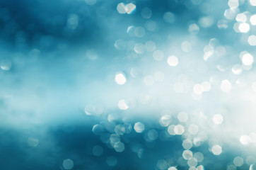 Christmas shiny glitter light bokeh in blue silver colors, seasonal holiday blurred background