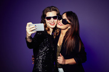 Smiling young women standing against dark background cheek to cheek and taking picture of themselves, waist-up portrait