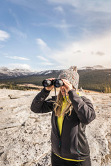 Woman looking through binoculars, Yosemite National Park, California, USA