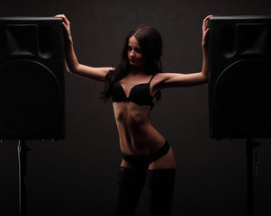 sexy young girl in lingerie dance between two big black speakers, front