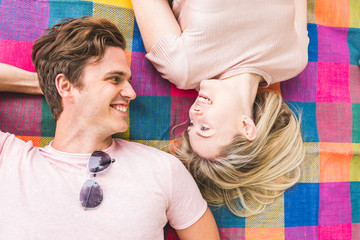 Couple lying on picnic blanket,resting on elbows, face to face, smiling
