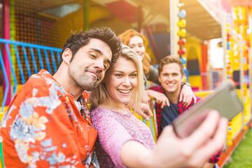 Friends taking selfie by carnival booth