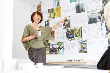 Architect pointing at photograph while giving presentation in office