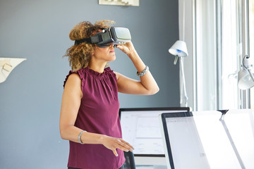 Female architect looking through virtual reality headset at office desk
